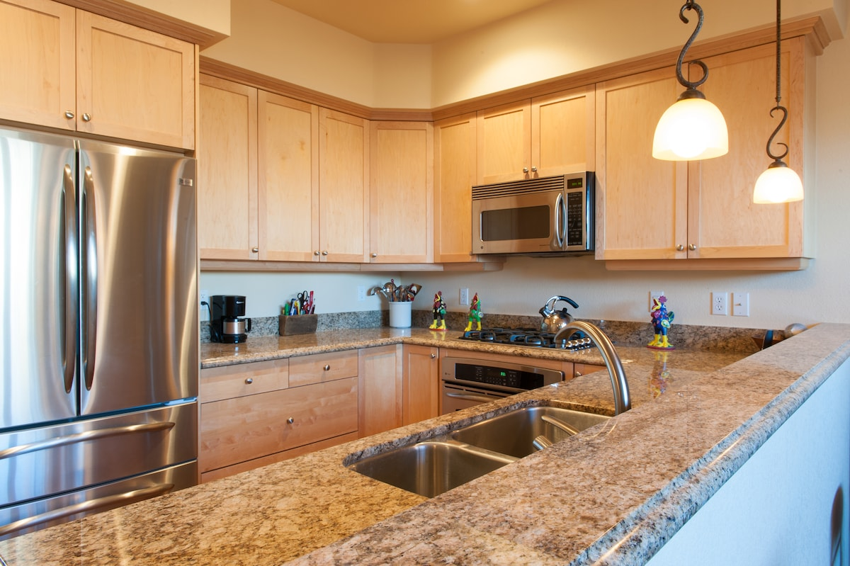 The kitchen contains stainless appliances and counters of slab granite.