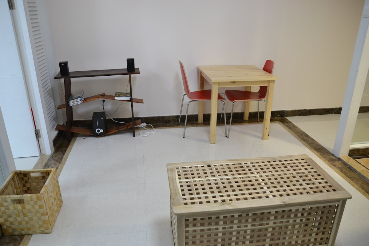 Living room with speakers and two person dining table.
