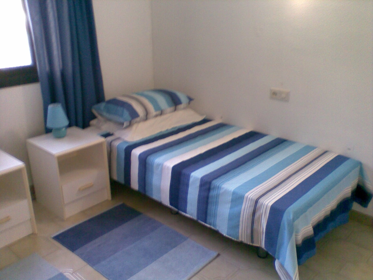 One of two full size single beds in second bedroom.
