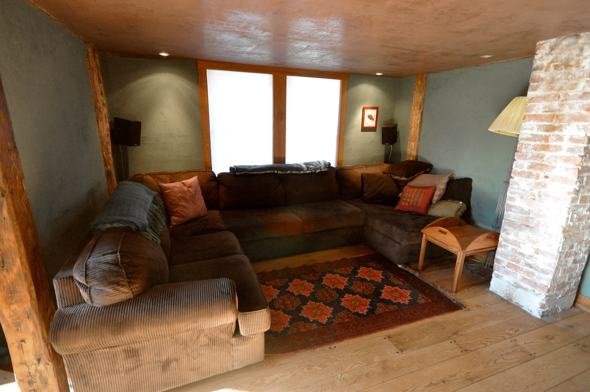 """Best room in the house: this cozy surround couch looks towards our 40"""" flatscreen with surround sound. Notice speakers set at ear level on the back wall. The low ceiling makes for great sound and cozy feeling."""