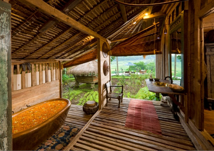 The oversized bathroom with a generous rain shower and an exquisite hand-hammered, indulgent copper tub. Note there are draw down blinds for privacy. Splendid view across the valley in the background