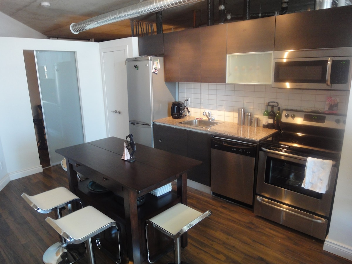 full kitchen with s/s appliances, granite, bar stools, island that converts ti dining table