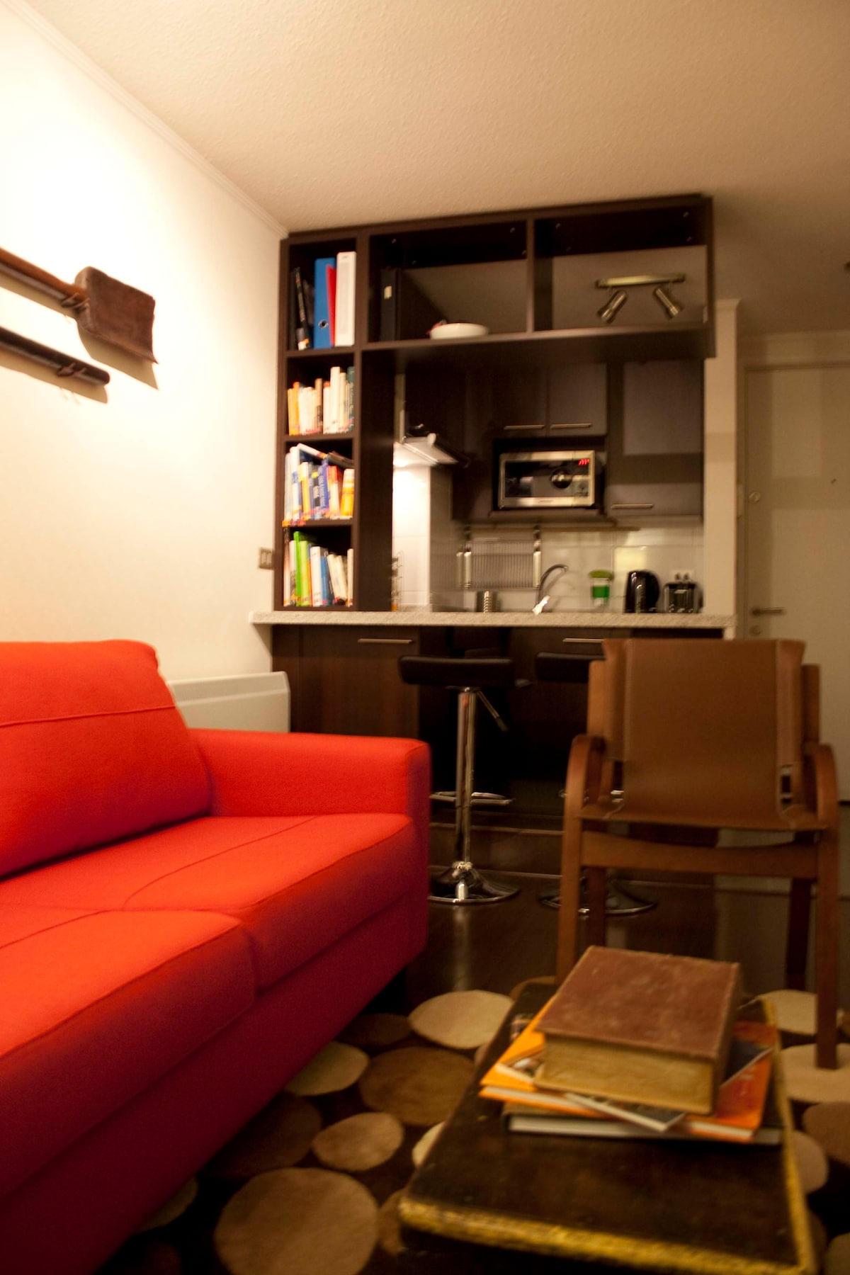 Living area, multilingual books about Chile and kitchen at night