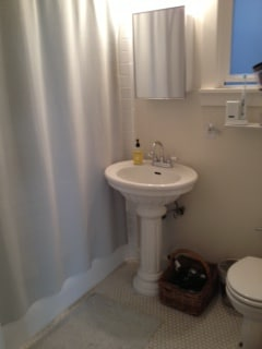 Bathroom is clean and decorated with Restoration Hardware furnishings.