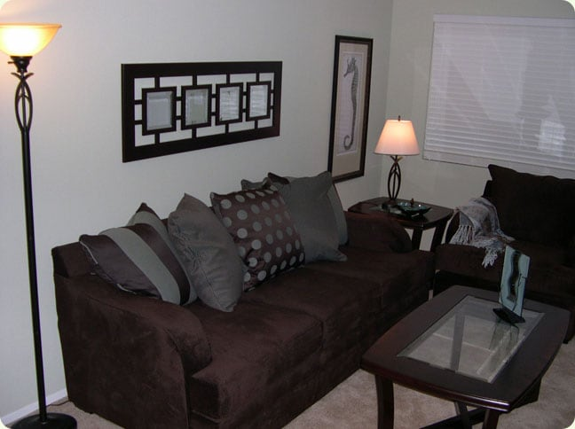 Living room seating, including large plush sofa with lots of decorative pillows, plus end table and comfy large chair
