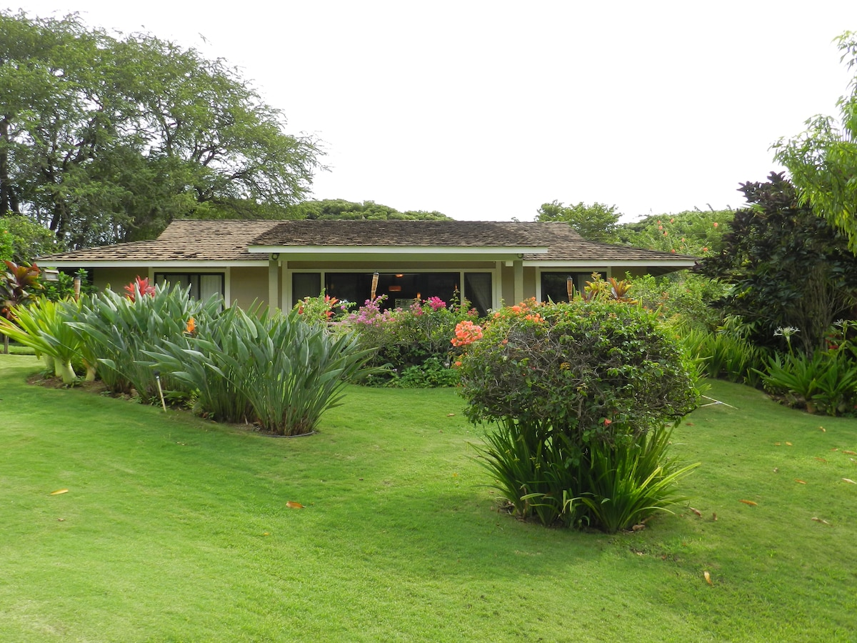 Three bedroom, two bath bungalow with mature tropical landscape in estate setting.