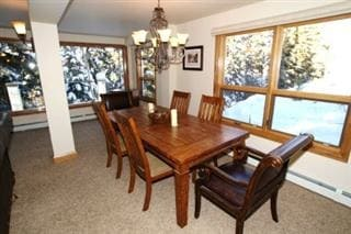 Dining room off of the living room. Tons of windows and light! Table has leaf for extra seating and extra chairs in storage closet.