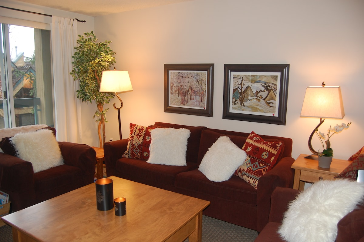 Spacious living room with large windows, gas fireplace, and balcony!