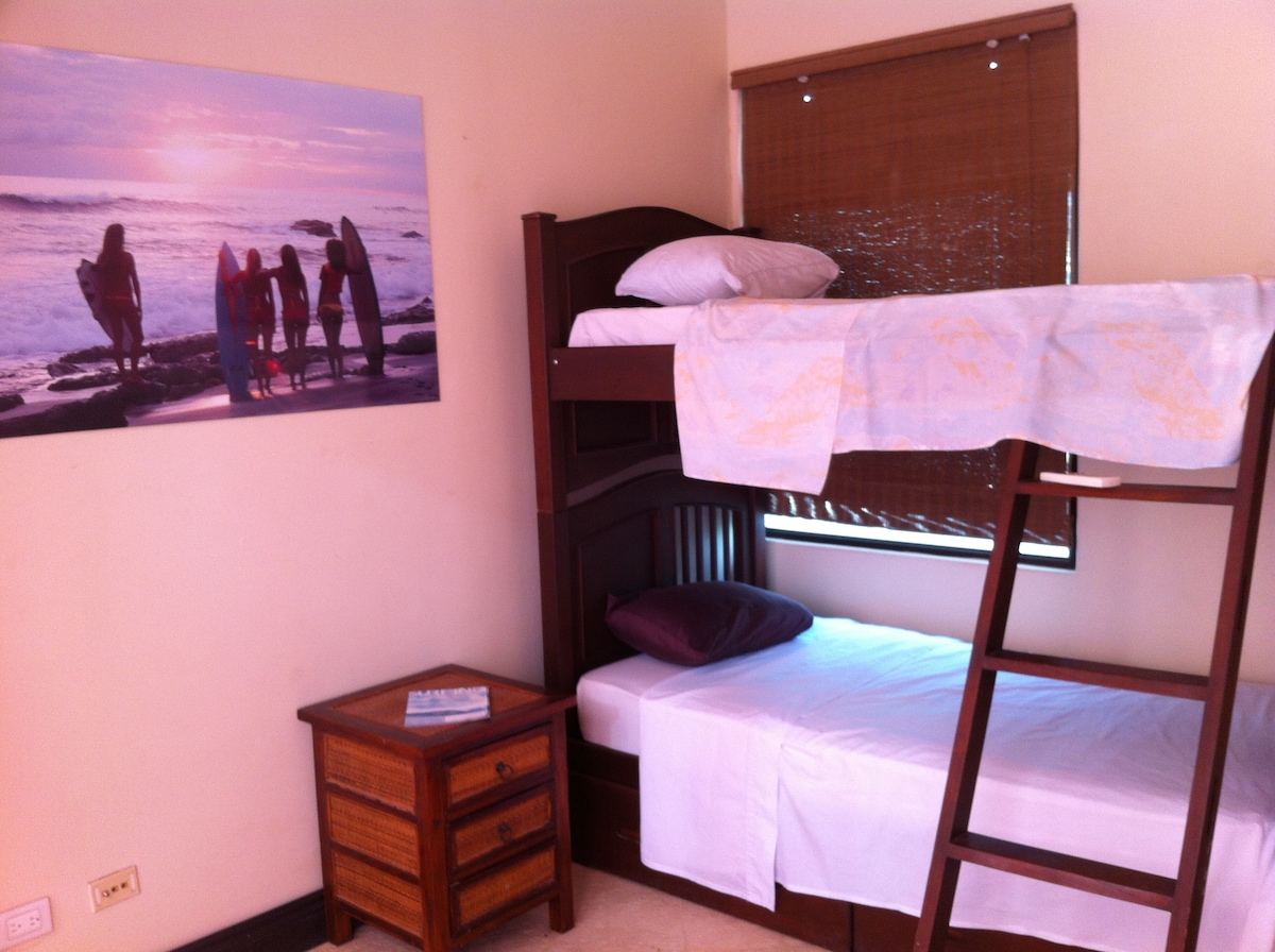 The smaller bedroom, with private bathroom, great light, AC, and sliding doors onto the sundeck.