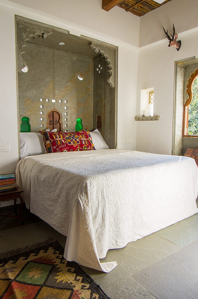 The super comfortable king size bed in the hand carved stone jarokha.