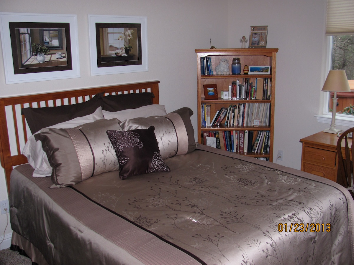 A second bedroom has a queen bed, desk, dresser, closet, & access to the guest bath with tub/shower.