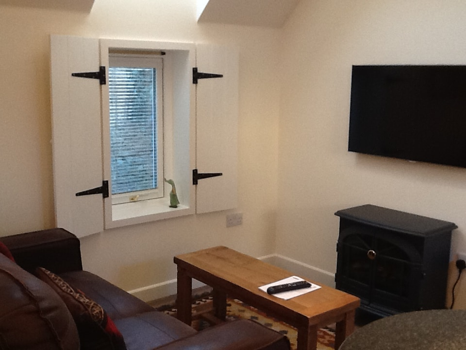 Living area with HDTV, warming fire and walled garden outlook