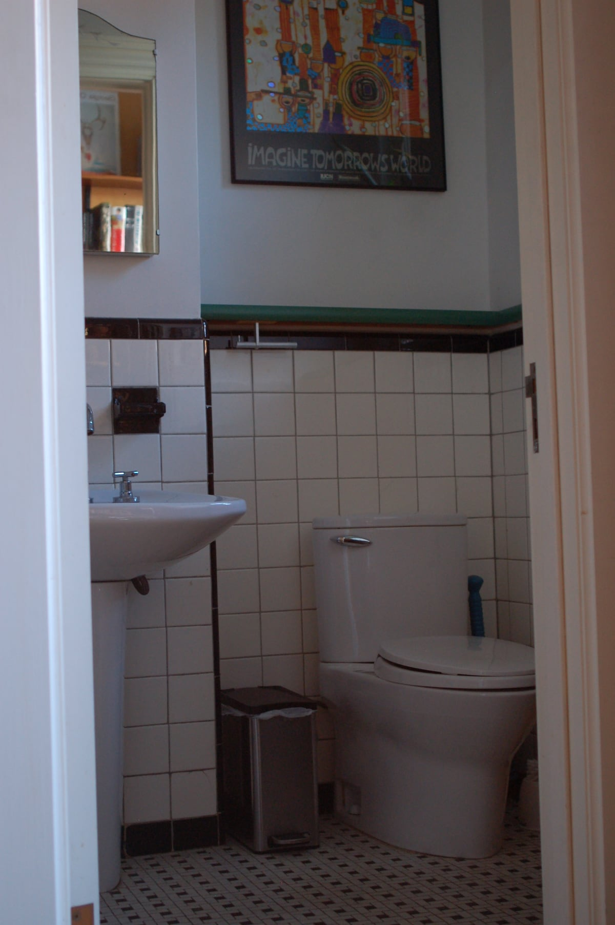 """Sink and toilet with Hundertwasser poster """"Imagine Tomorrow's World""""."""