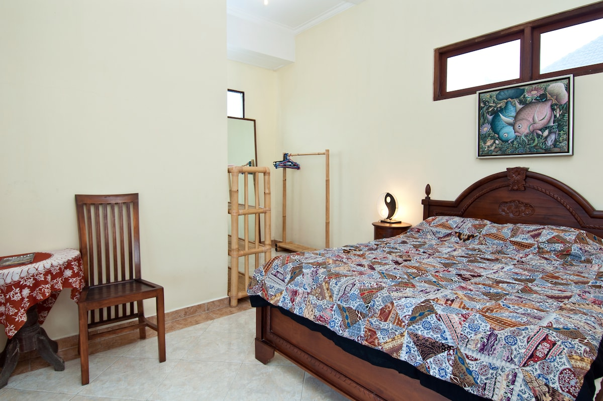 DI Atas bedroom has double bed and ample storage room. The painting above the bed is by Made Arka, homestay owner