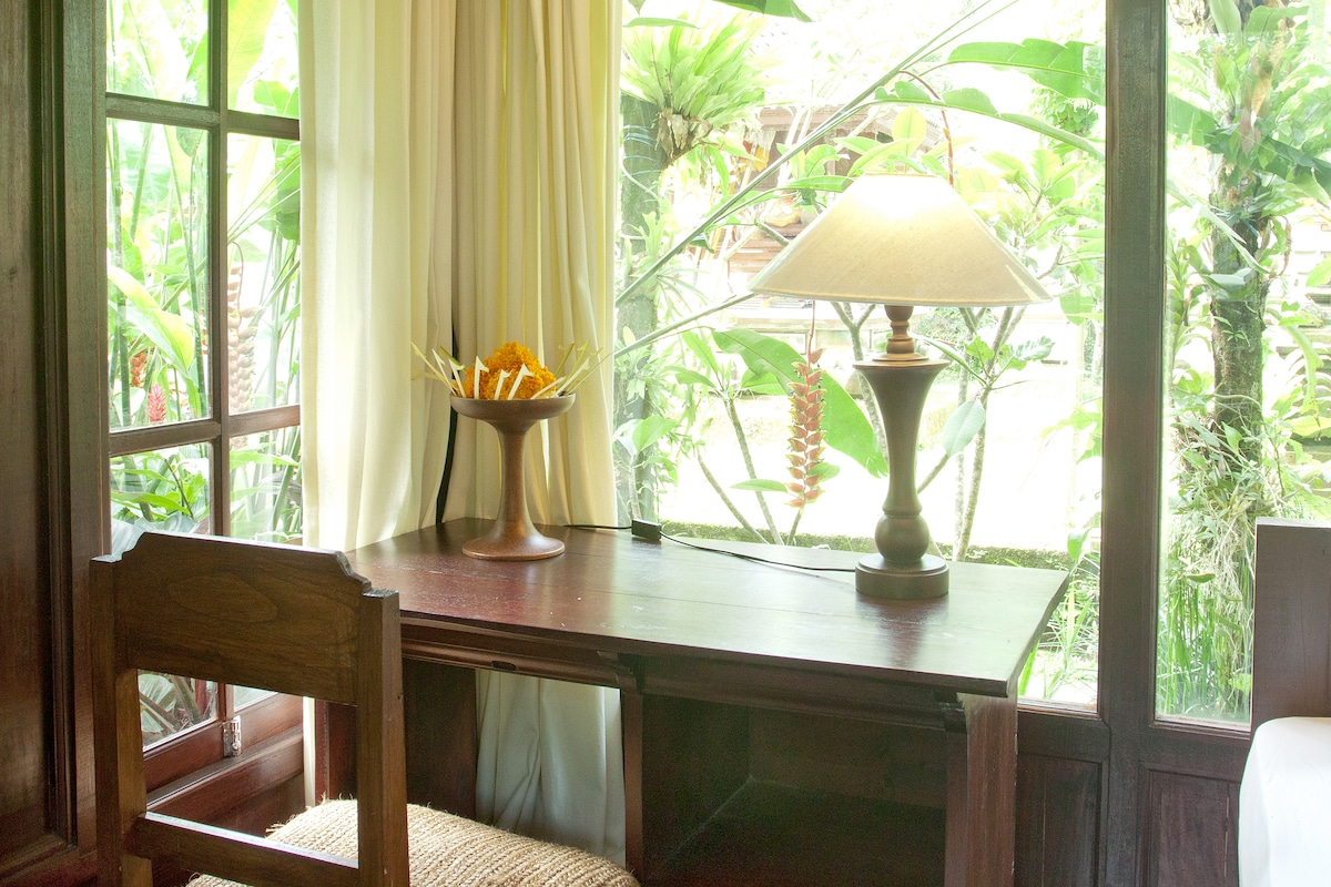 A small writing table with open view out to the garden and family shrines.