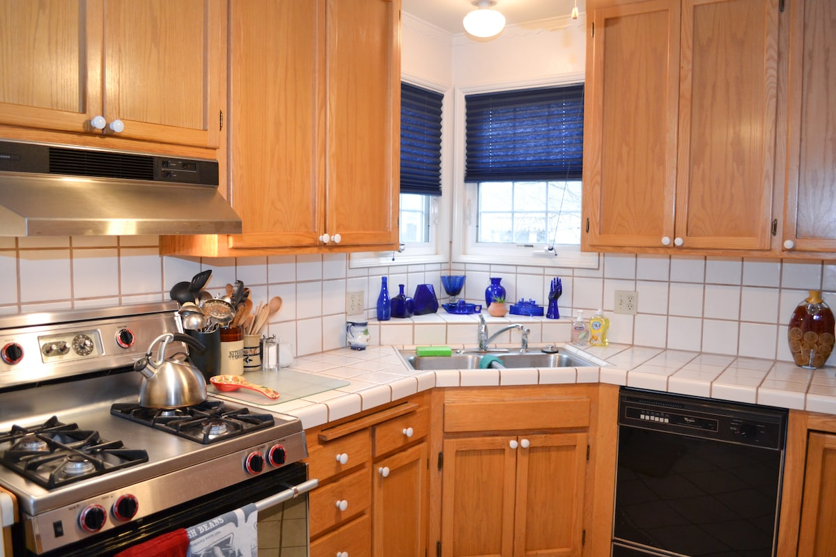 View of well lighted kitchen with tile counter tops, corner windows allowing for morning sun!