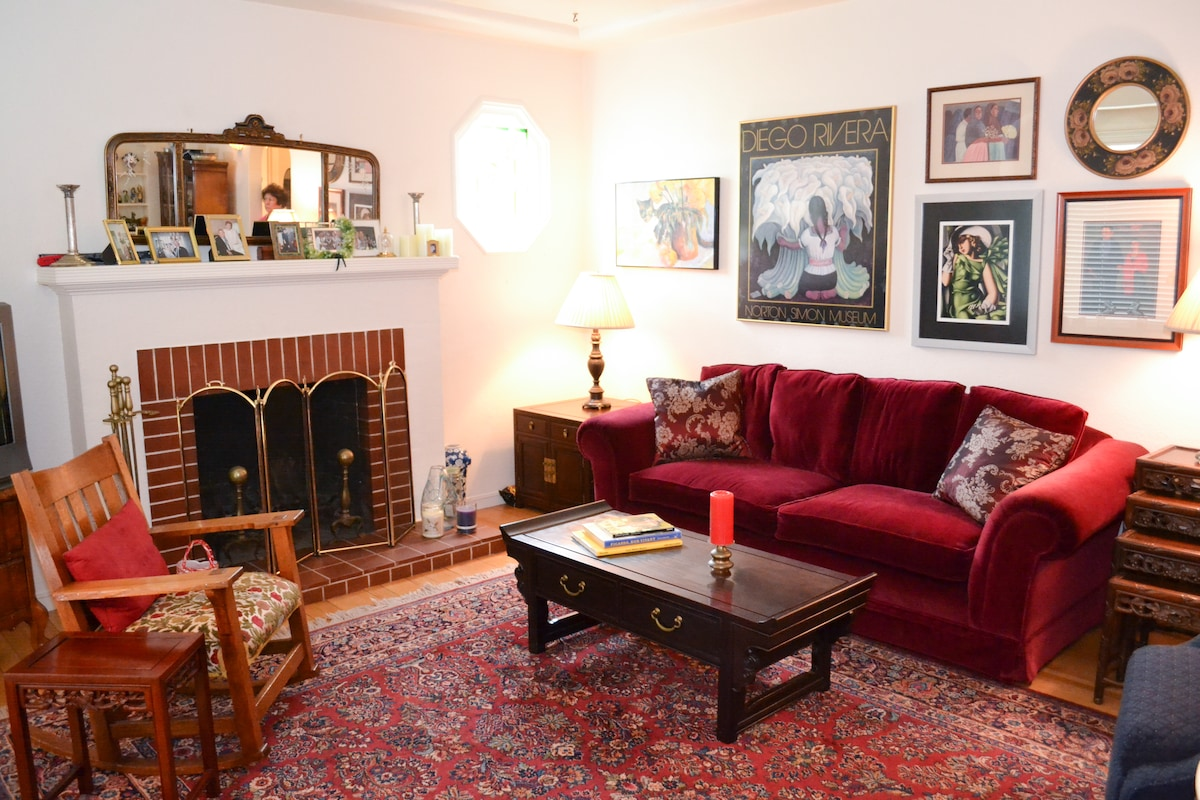 Living room with burgundy velvet sofa and Oriental carpet. Quality artwork on walls emphasizes the beautiful ambience of the home!