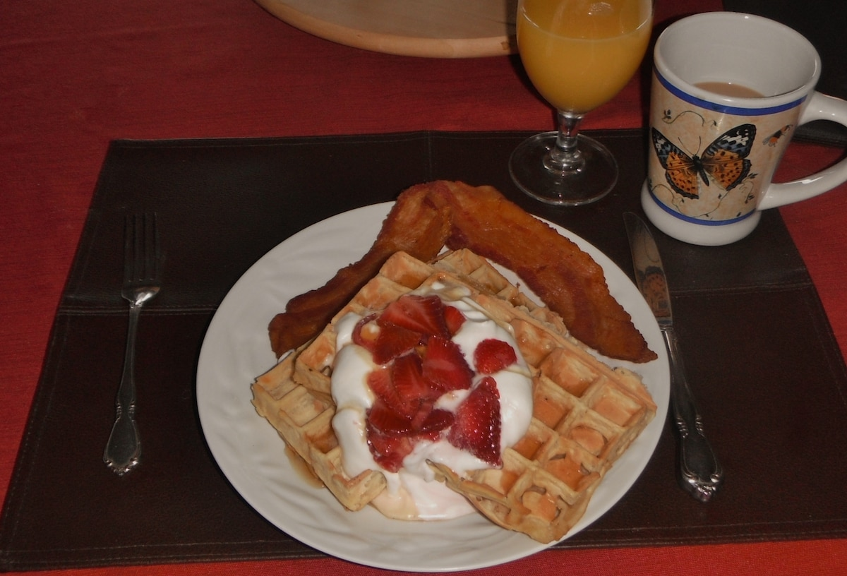 Belgium waffles with homemade whipped cream, syrup, fresh strawberries and bacon.