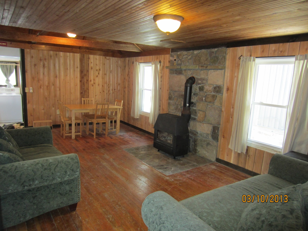 Living room with wood stove and dinning room from front door.