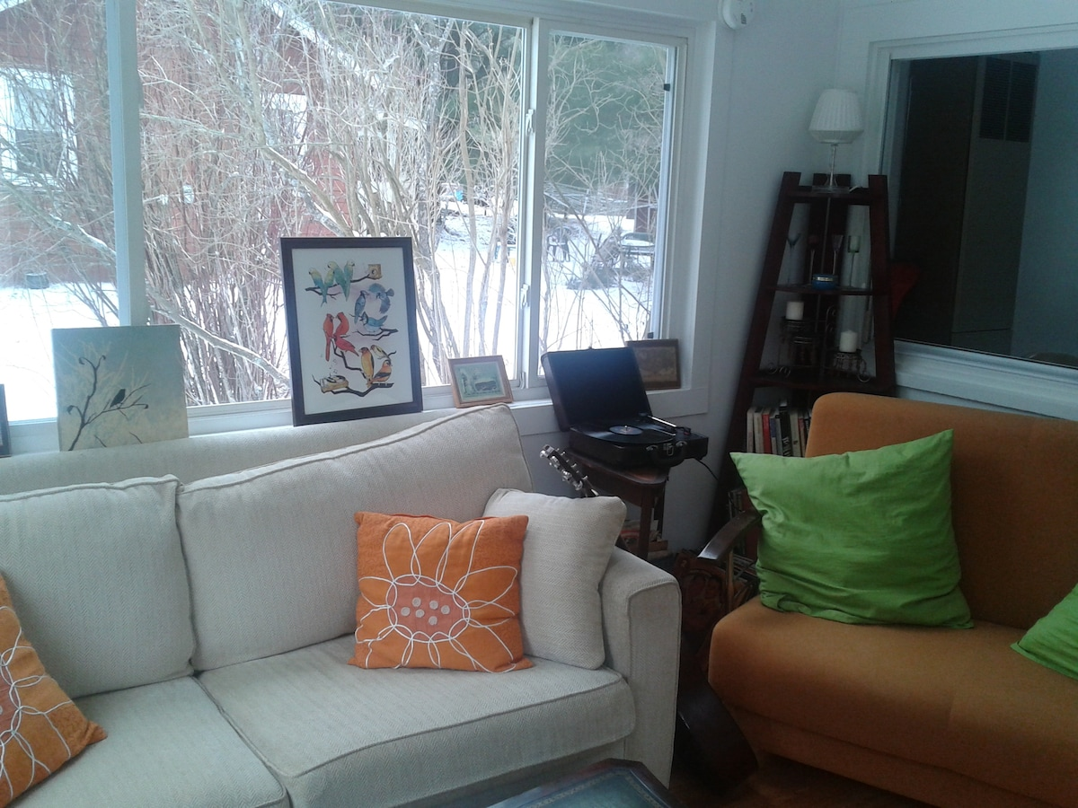The cozy, sunlit living room is perfect for reading or listening to records.