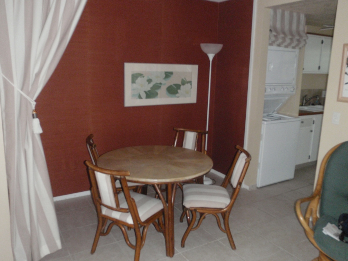 Dining area next to living room and kitchen
