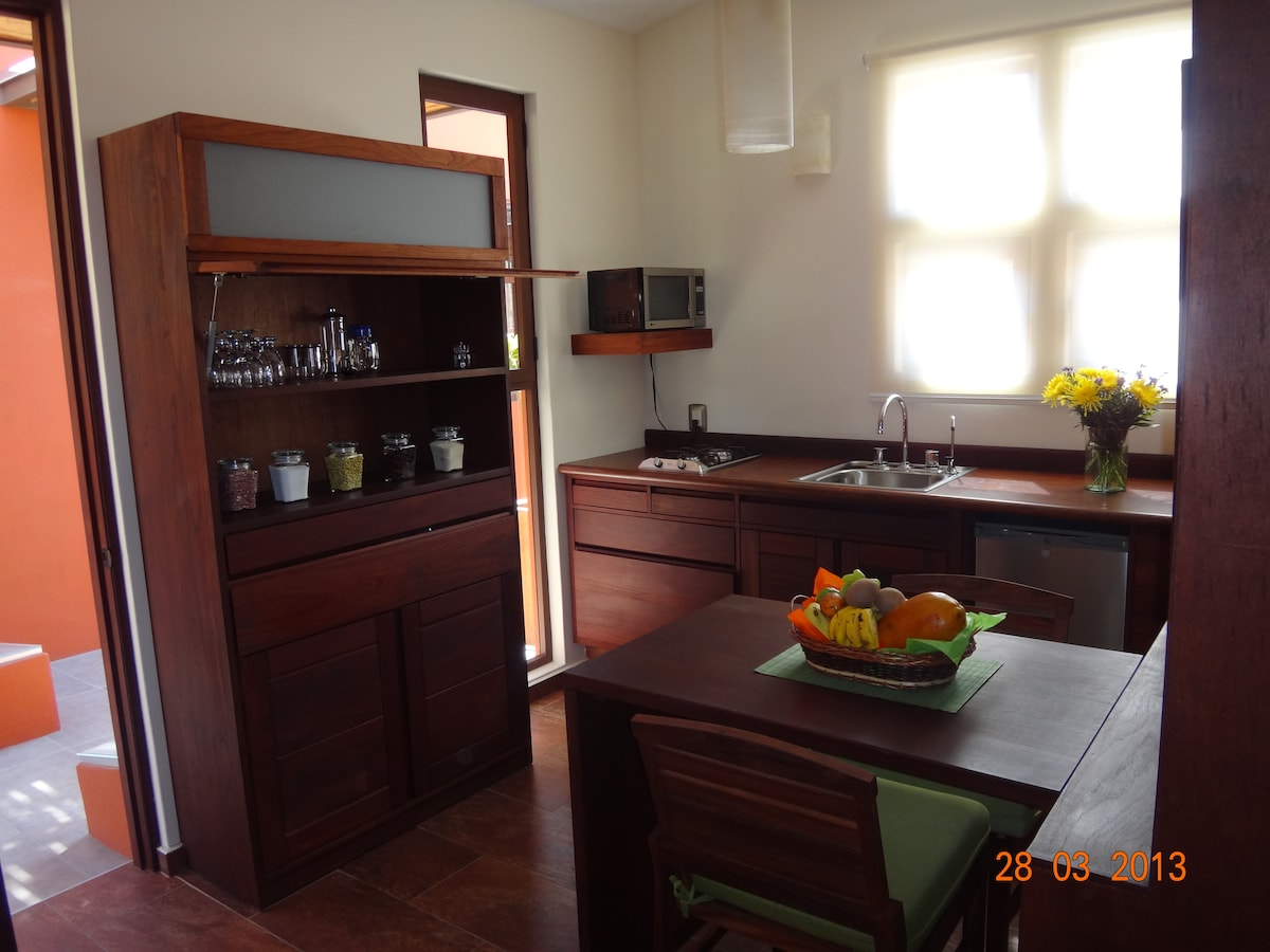 Kitchen with microwave, gas stove, refrigerator, dinning table, potable water