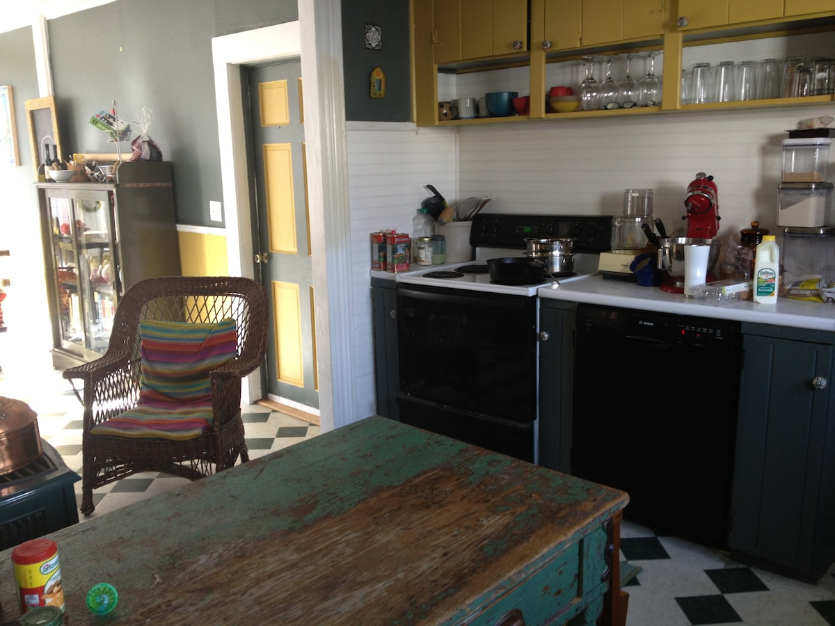 The working part of the kitchen, including farm table and comfortable chair for the sous chef.