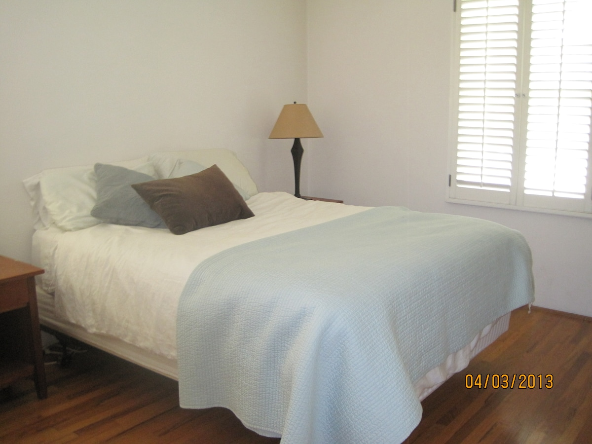 Bedroom with hard wood floors and queen bed