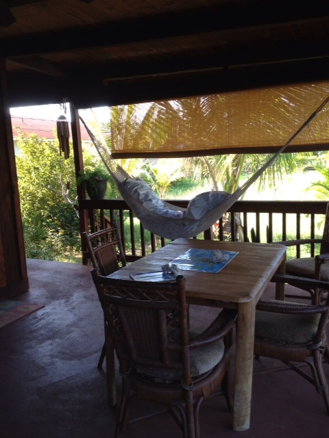 Indoor outdoor living...deck has dining table and chairs, hammock, rattan screens
