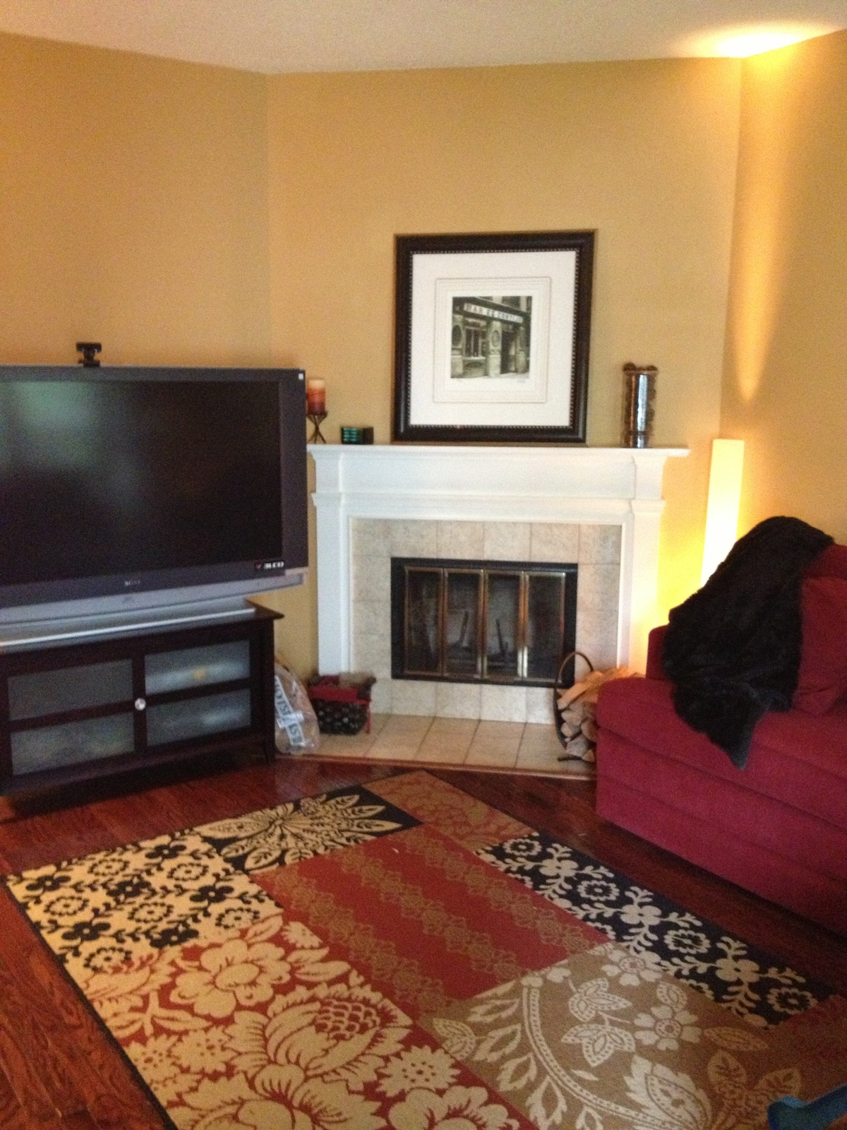 Living room with big screen TV, PlayStation 3 and fireplace.