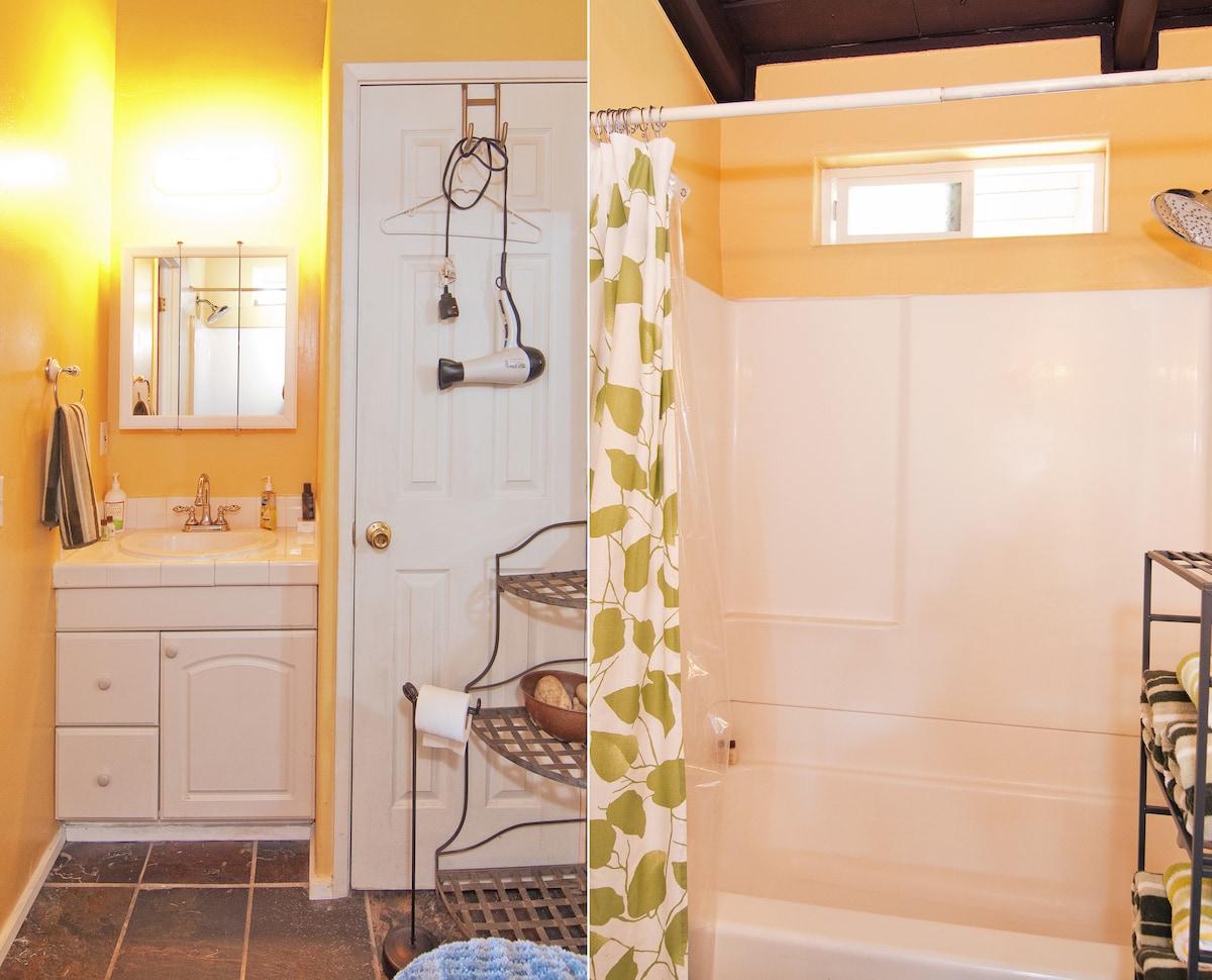 Rain style shower head and bathtub in bathroom.