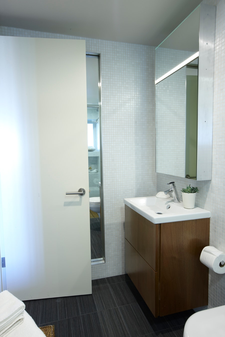 Bathroom. custom teak pull-out drawer vanity and Duravit fixtures; mirror cabinet with side lighting fixture; slide-open shelfing unit with full-length mirror for more storage.