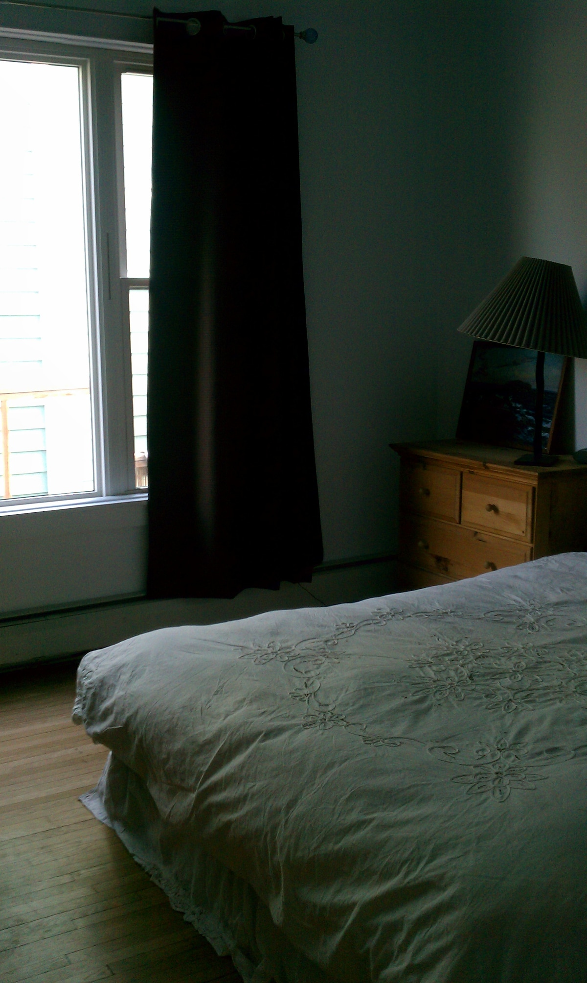 View of a part of the big picture window, queen bed and night stand in airbnb room.