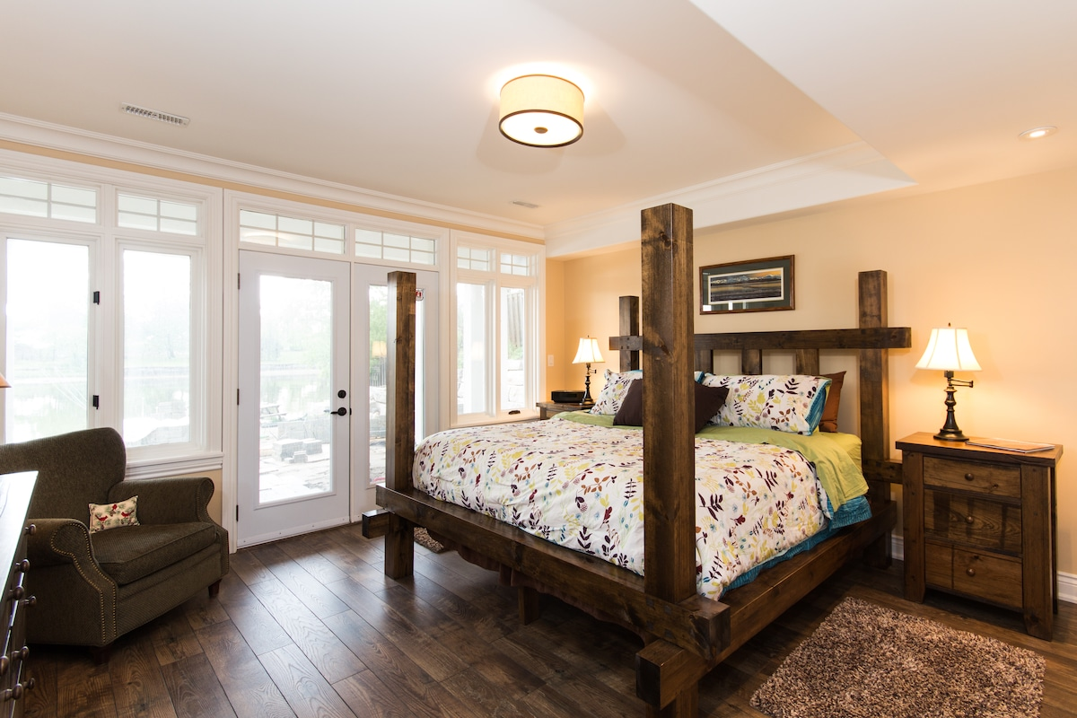 Bedroom with king size bed and walkout to river.