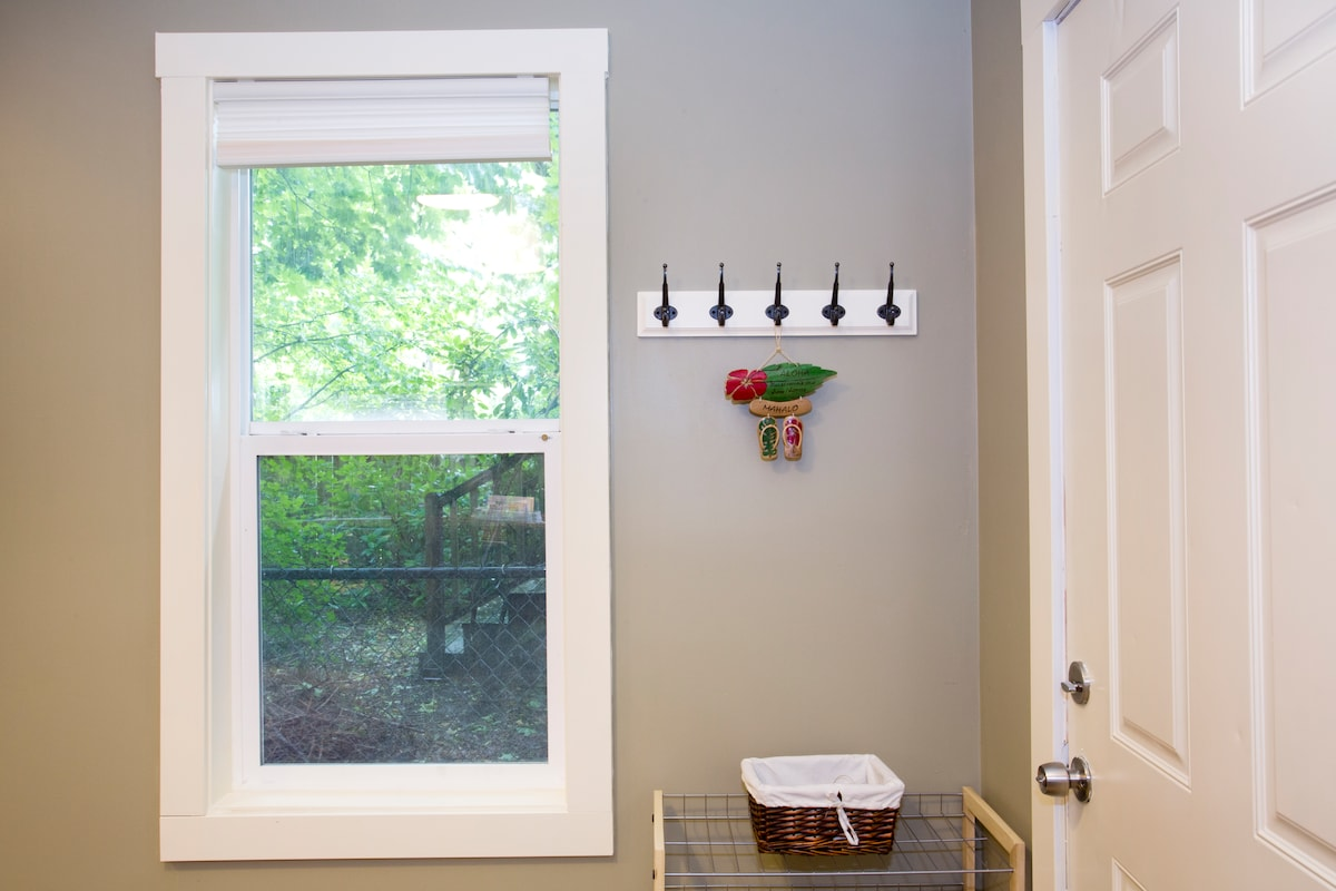 Dual pane windows with screens let the fresh air in from a densely tree-covered yard.
