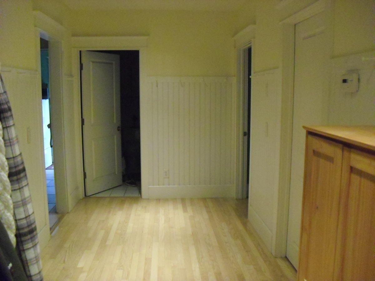 The hallway outside the guest room. Bathroom is straight ahead. The guest room is to the right.