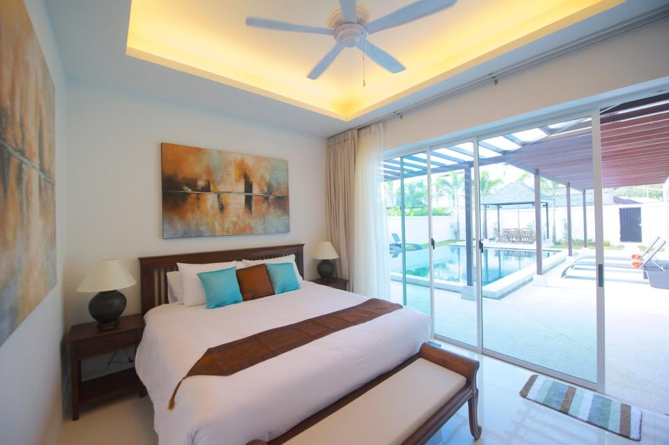 Bedroom 2 overlooks the pool and garden. It has an ensuite bathroom, ceiling fan and air-conditioning.