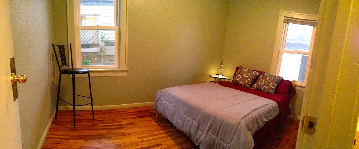 Quaint bedroom sparsely furnished.