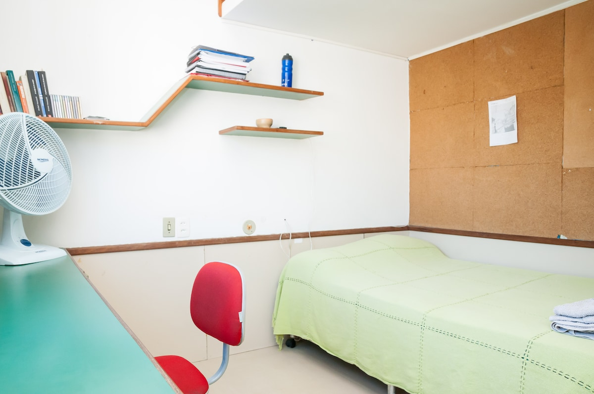Há várias prateleiras, uma bancada de trabalho e uma parede de cortiça para afixar decoração e lembretes
