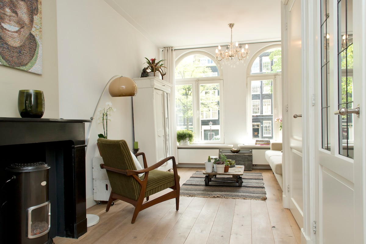 Bright and cosy living room with big arched windows overlooking the canal