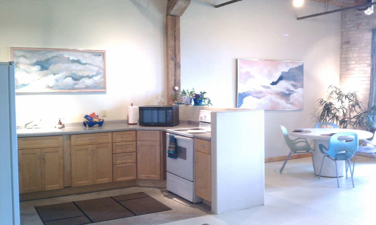 Dining room and kitchen with full stove/cooktop, microwave, fridge with ice in the door