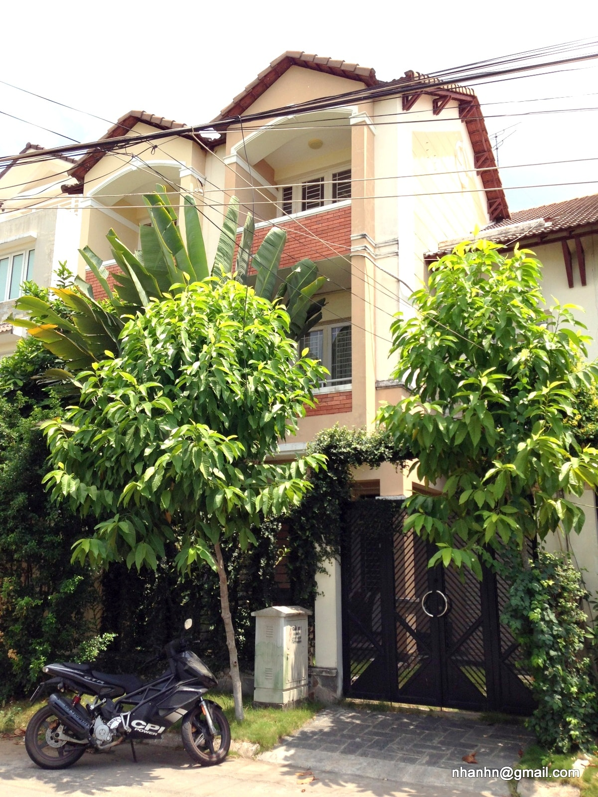 The 3-storey townhouse with the small garden in front, security guards are 10 meters away