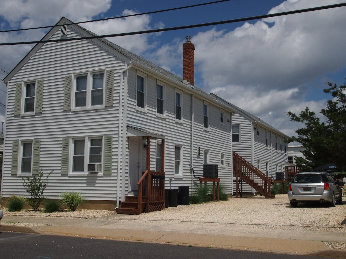 The rental apartment is the first floor unit of the front building.