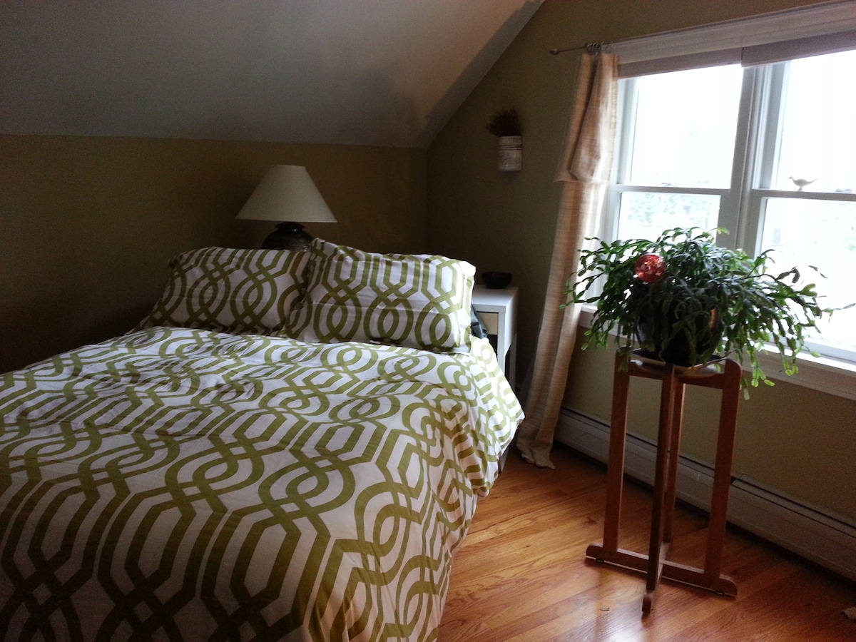 Spacious yet cozy room with lots of light, double bed, and puffy duvets