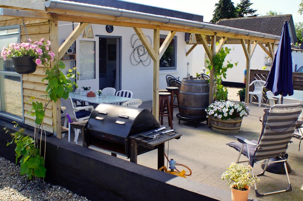 Man kan både holde fest og bare hygge omkring grillen på vores terrasse