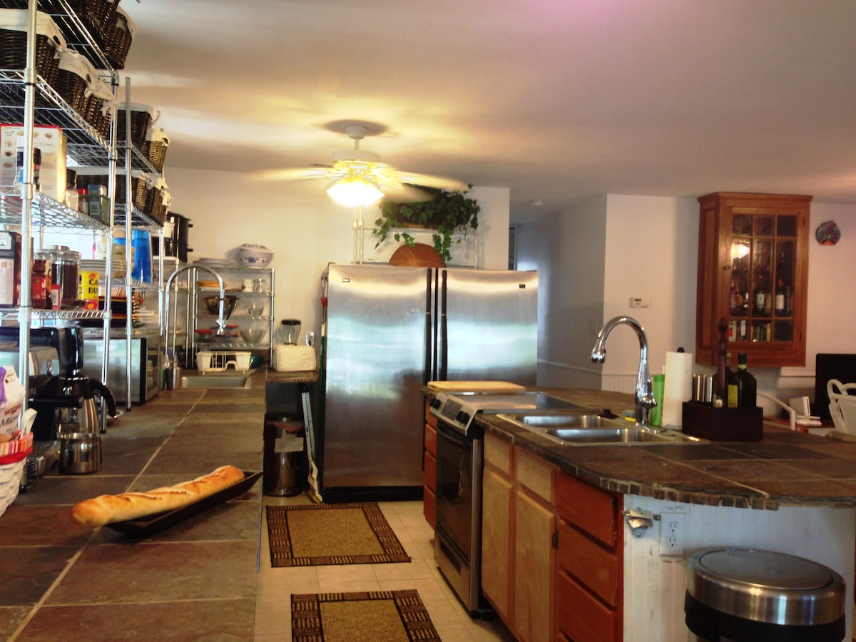 Gourmet commercial kitchen with: slate counters, commercial sinks, and island bar opening into the living room