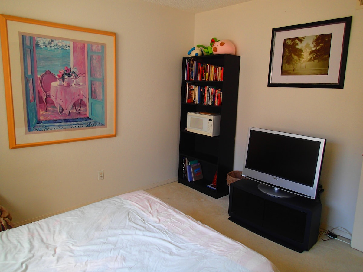 The room includes a TV, in-room microwave, and plenty of books to read.