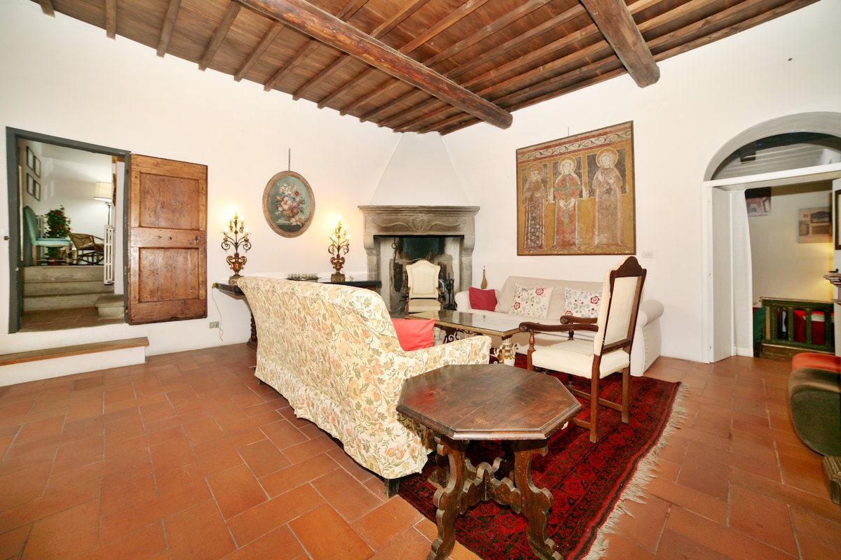 The Living Room with old tuscan traditional fireplace in pietra serena