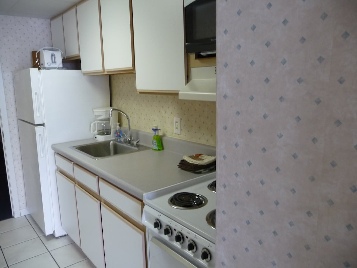 Kitchen with full size refrigerator, stove, oven,microwave and dishes.