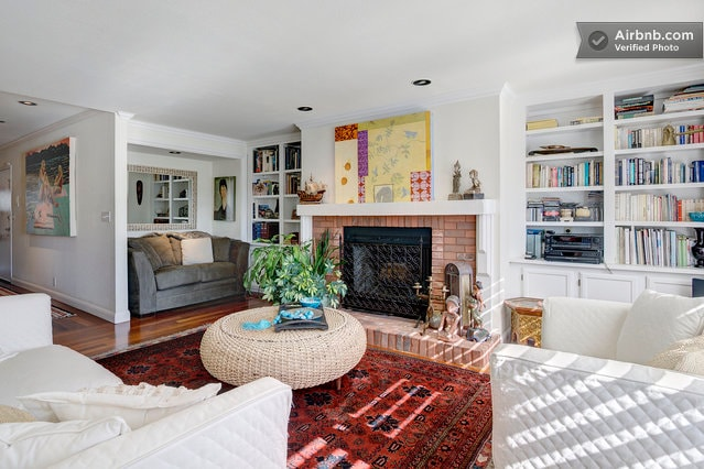 Living room with reading nook and fireplace with bookcases and entertainemnt center, hardwood floor, cosy and warm with great art.